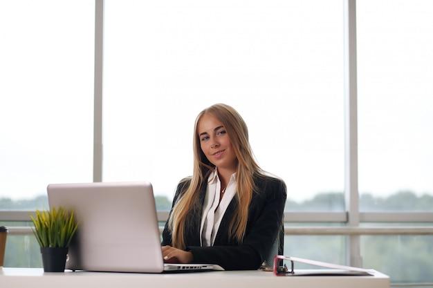 Elegancka Bizneswoman Siedzi W Swoim Biurze Premium Zdjęcia