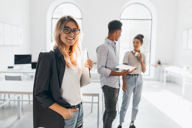 Elegancka Dama Biznesu W Modnej Czarnej Kurtce Trzymając Laptop I Uśmiechając Się. Portret Wesoła Blond Sekretarka I Wysoki Afrykański Pracownik Biurowy. Darmowe Zdjęcia