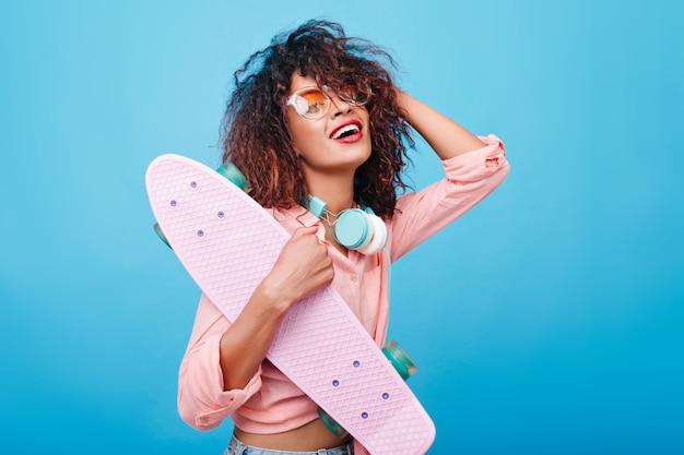 Elegancka Dziewczyna Afryki W Różowej Koszuli Na Sobie Duże Słuchawki I Stylowe Okulary Przeciwsłoneczne, Uśmiechając Się. Kryty Portret Czarnej Młodej Damy Z Kręconą Fryzurą Z Deskorolką. Darmowe Zdjęcia