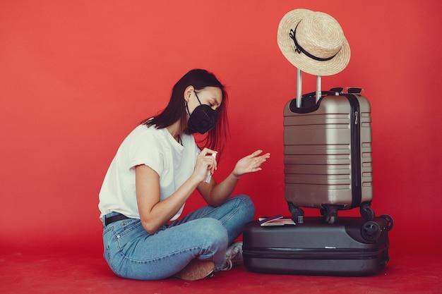 Elegancka Dziewczyna Pozuje Z Podróży Wyposażeniem Na Czerwonej ścianie Darmowe Zdjęcia