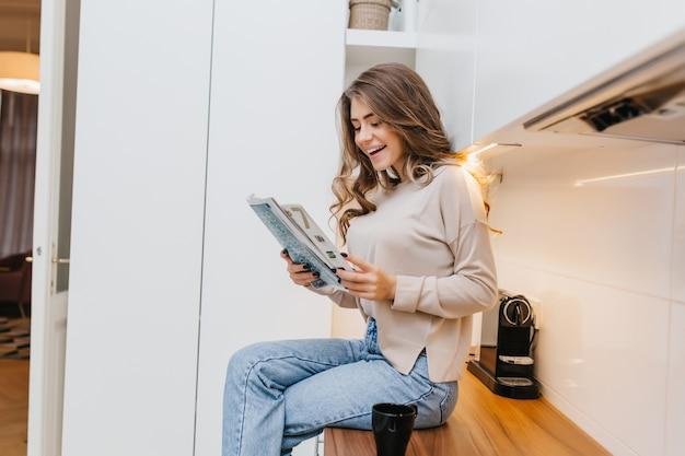 Elegancka Dziewczyna Z Długimi Włosami Siedzi Ze Skrzyżowanymi Nogami W Kuchni I Czyta Wiadomości Z Uśmiechem Darmowe Zdjęcia