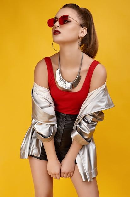 Elegancka glamour hipster dziewczyna w czerwonym topie, czarnych szortach i kurtce jeansowej Premium Zdjęcia
