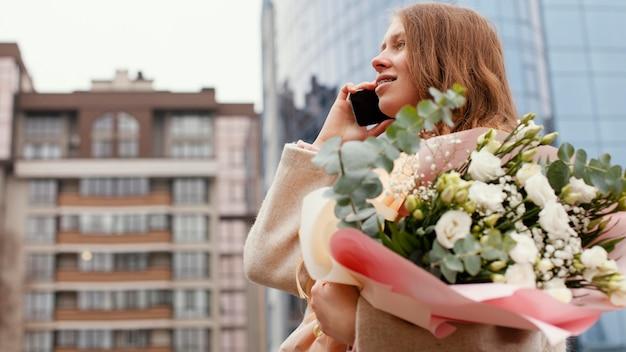 Elegancka Kobieta Na Zewnątrz Rozmawia Przez Telefon I Trzyma Bukiet Kwiatów Darmowe Zdjęcia