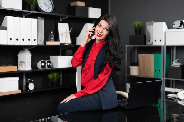 Elegancka kobieta usiadła na stole z laptopem w biurze i rozmawia przez telefon Premium Zdjęcia