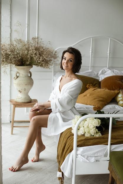 Elegancka Kobieta W Białej Sukni Pozuje I Siedzi Na Kanapie Darmowe Zdjęcia