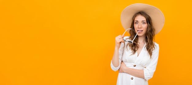 Elegancka Kobieta W Kapeluszu I Okularach Przeciwsłonecznych Pozuje Na Kolorze żółtym Premium Zdjęcia