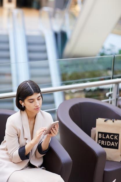 Elegancka Kobieta Za Pomocą Smartfona Podczas Relaksu W Centrum Handlowym Premium Zdjęcia