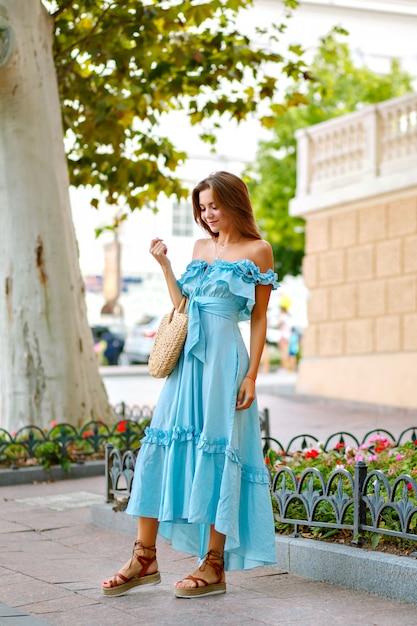Elegancka ładna Kobieta Ubrana W Modną Niebieską Sukienkę Maxi, Pozuje W Parku Miejskim Darmowe Zdjęcia