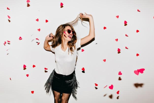 Elegancka Młoda Dama W Modnych Okularach Przeciwsłonecznych, Patrząc Na Upadłe Serca Darmowe Zdjęcia
