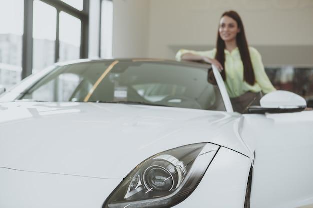 Elegancka młoda kobieta kupuje nowego samochód przy przedstawicielstwem handlowym Premium Zdjęcia