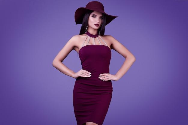 Elegancka Piękna Brunetka Kobieta W Fioletowej Sukience I Szerokim Kapeluszu Premium Zdjęcia