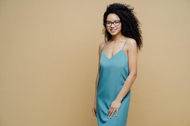 Elegancka Piękna Ciemnoskóra Kobieta Z Afro Włosami, Szczupła Sylwetka, Nosi Sukienkę, Stoi Wesoło Wewnątrz Na Beżowej ścianie Po Lewej Stronie Premium Zdjęcia