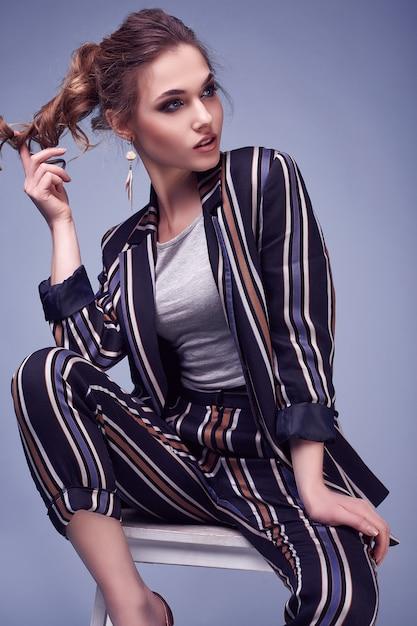 Elegancka Seksowna Kobieta W Moda Kostiumu Pozuje Na Kolorowym Błękicie Premium Zdjęcia