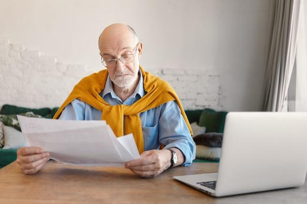 Elegancki Brodaty Starszy Mężczyzna W Prostokątnych Okularach Studiuje Kartki Papieru W Dłoniach, Oblicza Finanse Domowe Online W Domu, Korzysta Z Elektronicznego Urządzenia Przenośnego We Wnętrzu Salonu Darmowe Zdjęcia