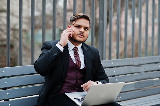 Elegancki Indyjski Biznesmen W Formalnej Odzieży Obsiadaniu Na ławce Z Laptopem I Mówieniu Na Telefonie Komórkowym. Premium Zdjęcia