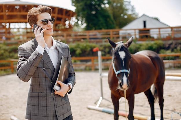 Elegancki Mężczyzna Stojący Obok Konia Na Ranczo Darmowe Zdjęcia
