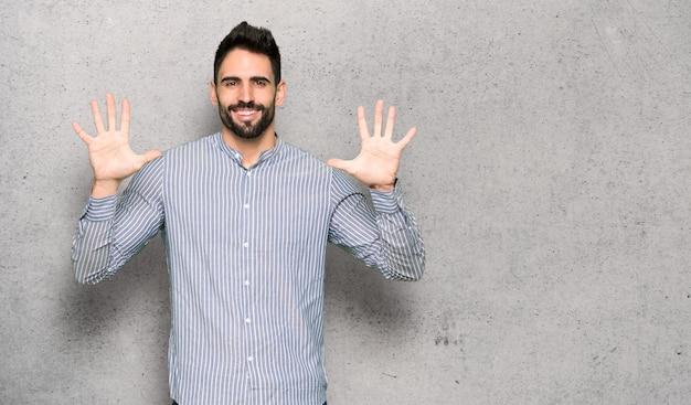 Elegancki Mężczyzna Z Koszula Liczy Dziesięć Z Palcami Nad Textured ścianą Premium Zdjęcia