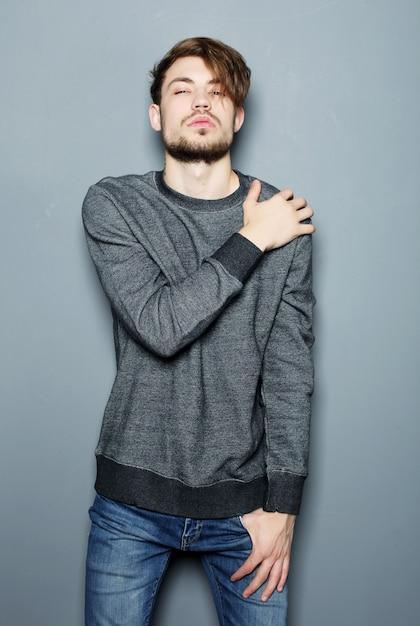 Elegancki Młody Przystojny Mężczyzna. Studio Moda Portret Na Szarej Przestrzeni Premium Zdjęcia