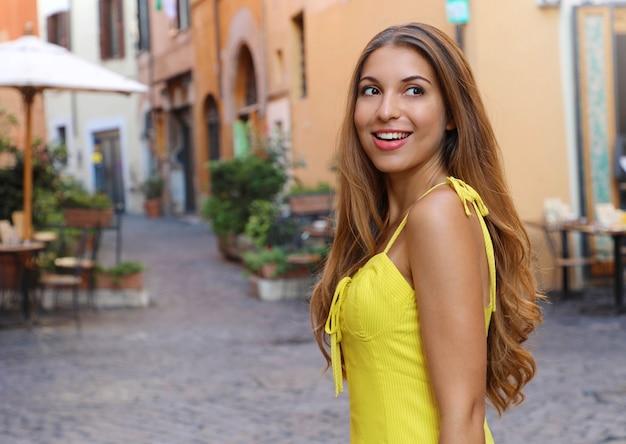 Elegancki Portret Pięknej Kobiety Moda Z Długimi Włosami W żółtej Letniej Sukience Spaceru W Dzielnicy Trastevere Rzym, Włochy. Premium Zdjęcia