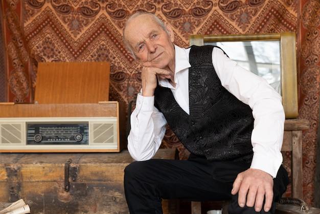 Elegancki Starszy Mężczyzna Oparł Się Na Dłoni I Spojrzał W Kamerę, Siedząc W Swoim Pokoju Premium Zdjęcia