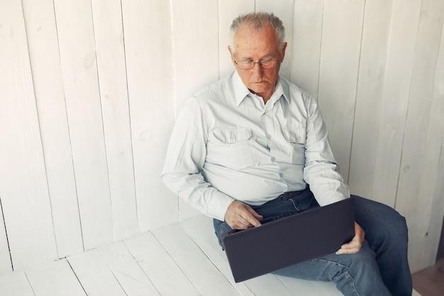 Elegancki Stary Człowiek Siedzi W Domu I Używa Laptopa Darmowe Zdjęcia
