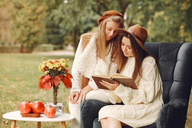 Eleganckie i stylowe dziewczyny siedzą na krześle w parku Darmowe Zdjęcia
