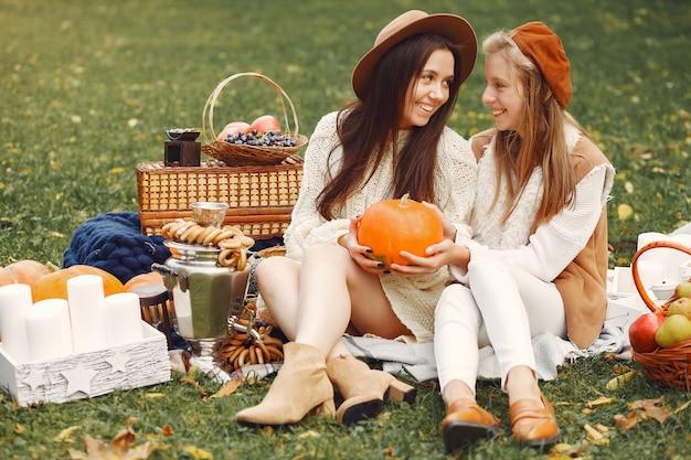 Eleganckie i stylowe dziewczyny siedzą w jesiennym parku Darmowe Zdjęcia