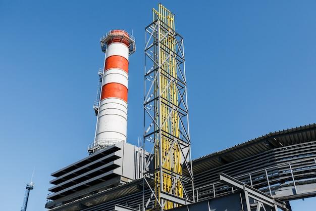 Elektrowni turbiny gazowej na gaz ziemny z kominami czerwony biały kolor na tle błękitnego nieba w słoneczny dzień Premium Zdjęcia