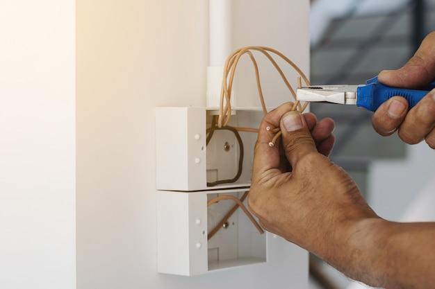 Elektrycy Używają Klucza Szczypiec Do Zainstalowania Wtyczki Na ścianie. Premium Zdjęcia