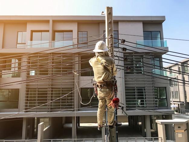 Elektrycy wspinają się na słupach elektrycznych, aby zainstalować linie energetyczne. Premium Zdjęcia