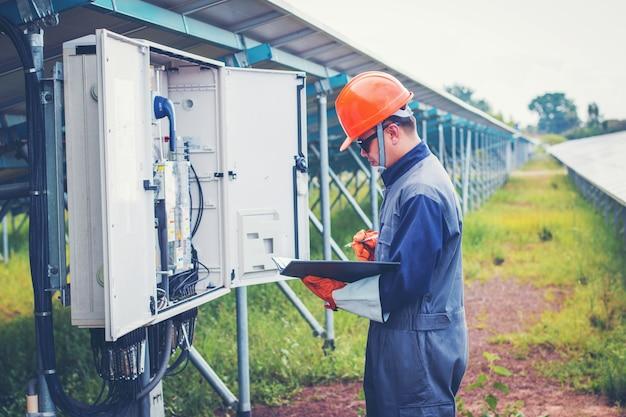 Elektryk pracujący przy sprawdzaniu i sprawdzaniu urządzeń z listą kontrolną w branży zewnętrznej Premium Zdjęcia
