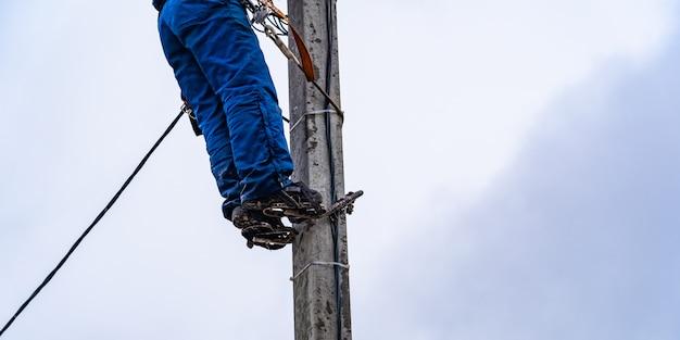 Elektryk vysotnik wykonuje instalację sieci elektroenergetycznych Premium Zdjęcia