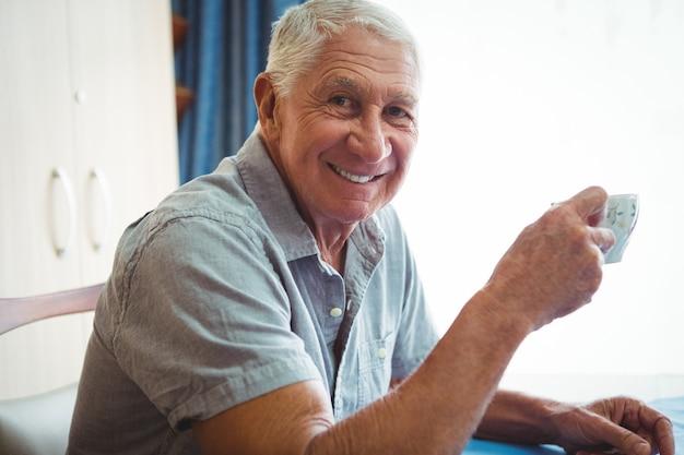 Emerytowany Uśmiechnięty Mężczyzna Trzyma Filiżankę Herbaty Premium Zdjęcia
