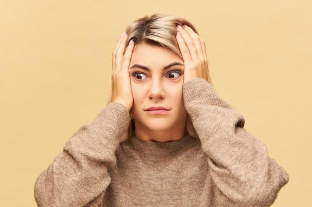 Emocjonalna Młoda Kobieta W Dużym Wygodnym Swetrze Trzymająca Się Za Ręce W Panice I Szoku, Wyglądająca Na Zapominalską. Sfrustrowana Nerwowa Dziewczyna Wariuje I Martwi Się, Ponieważ Schrzaniła Darmowe Zdjęcia