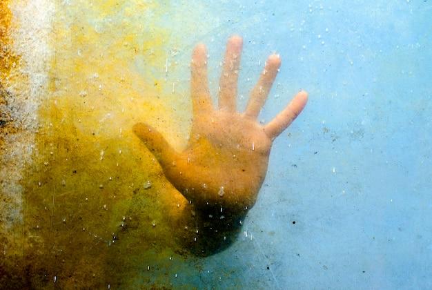 Emocjonalna ręka za brudną teksturą szkła Premium Zdjęcia