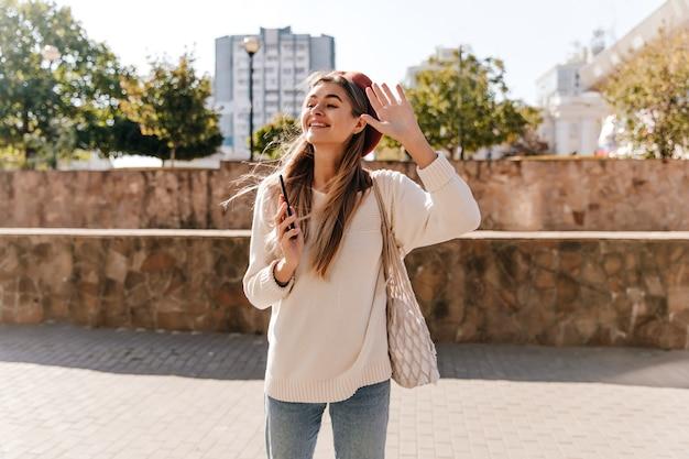 Emocjonalne Modelki W Berecie Macha Ręką Na Tle Miasta. Wesoła Dobrze Ubrana Pani Odpoczywa Na świeżym Powietrzu W Jesienny Dzień. Darmowe Zdjęcia