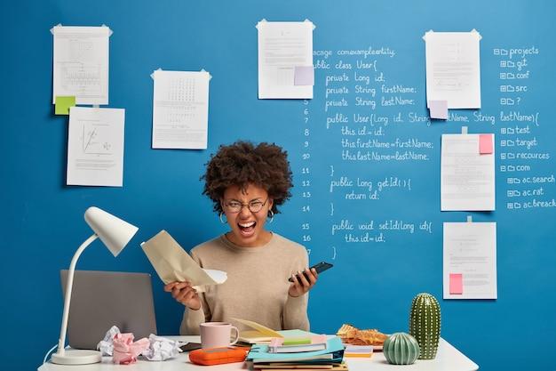 Emocjonalnie Wściekła Afroamerykanka Trzyma Papierowy Dokument I Telefon Komórkowy, Sfrustrowana Niepowodzeniem W Realizacji Projektu. Darmowe Zdjęcia