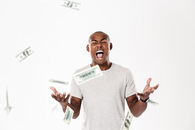 Emocjonalny Krzyczący Młody Afrykański Mężczyzna Z Pieniądze. Darmowe Zdjęcia