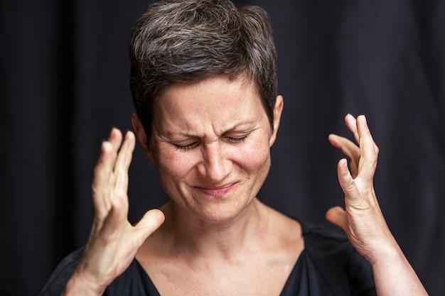 Emocjonalny Portret Dorosłej Kobiety Z Krótkimi Włosami I Zamkniętymi Oczami. Czarne Tło. Premium Zdjęcia