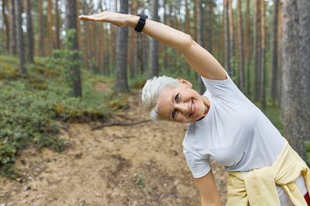 Energiczna, Aktywna Kobieta W średnim Wieku Rozgrzewa Ciało Przed Biegiem, Pozując Na Tle Sosen Darmowe Zdjęcia