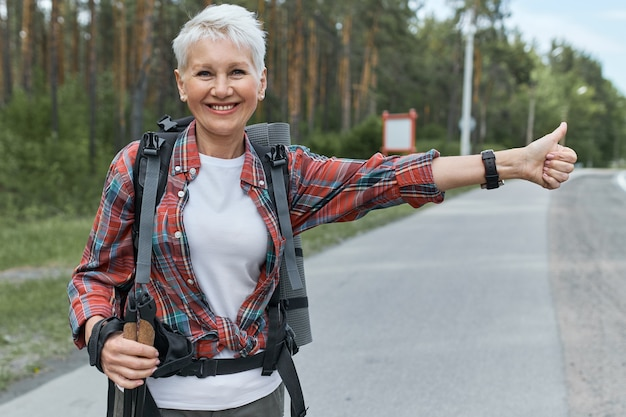 Energiczna Kobieta Pesnioner W Aktywnym Stroju, Stojąca Na Drodze Z Plecakiem Za Plecami, Autostopująca, Machająca Kciukami Do Góry, Sygnalizująca, że Potrzebuje Podwózki. Darmowe Zdjęcia