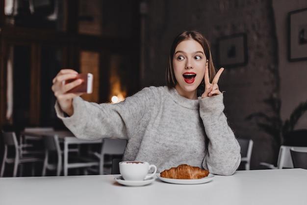 Energiczna Kobieta W Szarym Swetrze I Czerwonej Szmince Robi Selfie. Portret Dziewczynki Pokazano Znak Pokoju W Kawiarni Z Rogalikiem Na Stole. Darmowe Zdjęcia