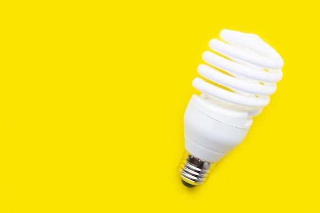 Energooszczędna żarówka na żółtym tle. Premium Zdjęcia