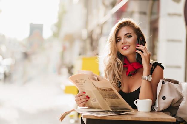 Entuzjastyczna Dziewczyna Kręcone Patrząc Z Uśmiechem Podczas Rozmowy Telefonicznej W Kawiarni Na świeżym Powietrzu Darmowe Zdjęcia