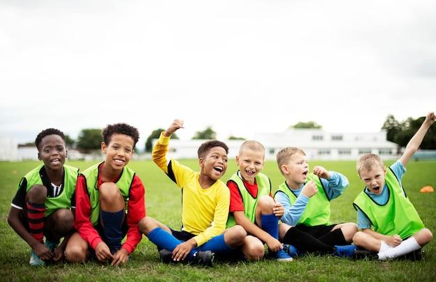 Entuzjastyczni piłkarze siedzą na boisku Premium Zdjęcia