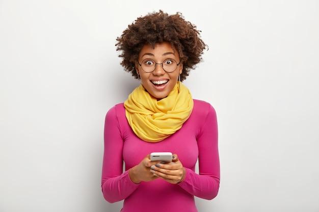 Entuzjastycznie Rozbawiona, Kręcona Młoda Kobieta Trzyma Nowoczesny Telefon Komórkowy, Czyta Sms, Nosi Okulary I Różowy Golf, Pozuje Na Białym Tle. Koncepcja Technologii Darmowe Zdjęcia