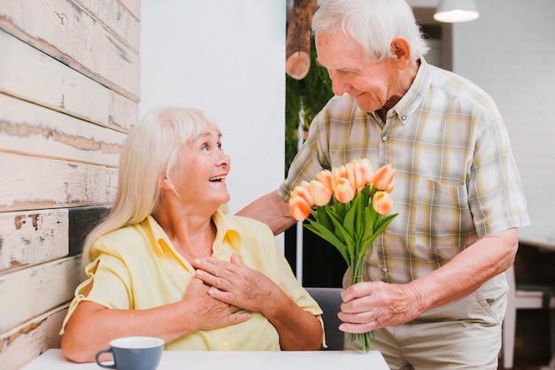 Entuzjastyczny starszy mężczyzna przedstawia kwiaty kobieta w kawiarni Darmowe Zdjęcia