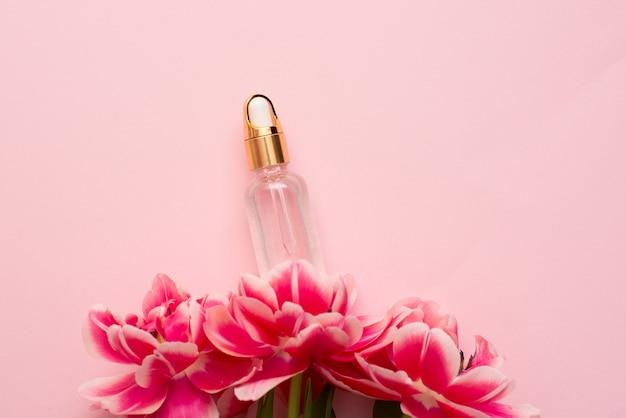Eteryczny Olejek Kosmetyczny Na Różowej Powierzchni Z Wiosennymi Kwiatami Premium Zdjęcia