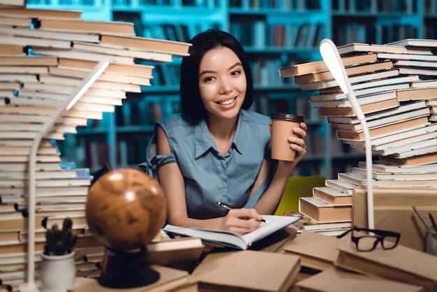 Etniczna Azjatykcia Dziewczyna Otaczająca Książkami W Bibliotece. Student Pisze W Zeszycie. Premium Zdjęcia