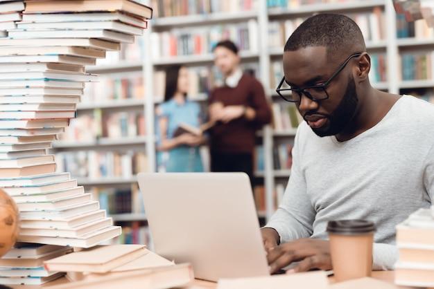 Etniczny Amerykanina Afrykańskiego Pochodzenia Facet Otaczający Książkami W Bibliotece. Student Korzysta Z Laptopa I Pije Kawę. Premium Zdjęcia